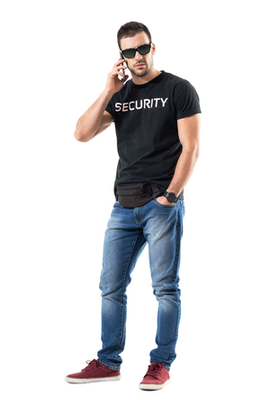 Tough serious undercover policeman talking on the phone looking at camera. Full body length portrait isolated on white studio background. Stock Photo