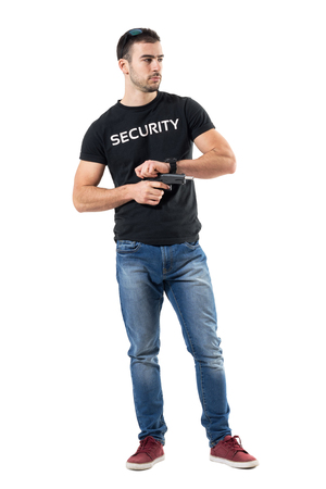 Undercover policeman cocking gun looking away.  Full body length  portrait isolated on white studio background.