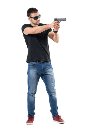 Young plain clothes policeman with sunglasses aiming gun away. Side view. Full body length  portrait isolated on white studio background. Stock Photo
