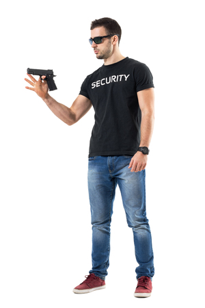 Young plain clothes policeman spinning gun on finger.  Full body length  portrait isolated on white studio background.