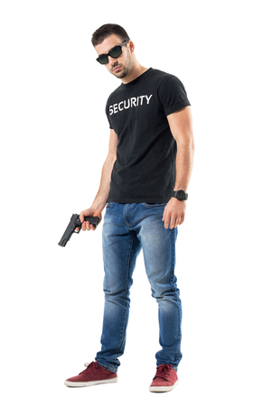 Tough confident plain clothes officer with sunglasses holding gun looking at camera.  Full body length  portrait isolated on white studio background.