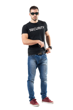 Undercover police man taking handgun from belt looking at camera.  Full body length  portrait isolated on white studio background.