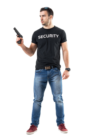 Alerted cautious plain clothes policeman holding gun looking away.  Full body length  portrait isolated on white studio background.