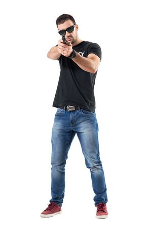 Plain clothes undercover cop aiming gun at viewer wearing sunglasses.  Full body length  portrait isolated on white studio background. Stock Photo