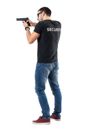 Side rear view of security guard pointing and aiming gun away.  Full body length  portrait isolated on white studio background. Reklamní fotografie