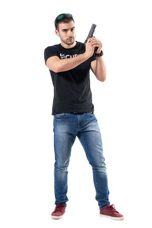 Serious cautious policeman in plain clothes holding gun with both hands.  Full body length  portrait isolated on white studio background.