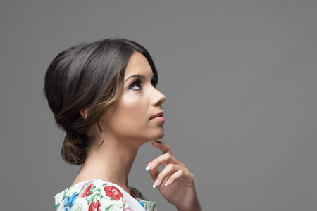 Gorgeous profile of latin hispanic beauty woman with finger under chin thinking and looking up at copyspace over gray studio background. Stock Photo