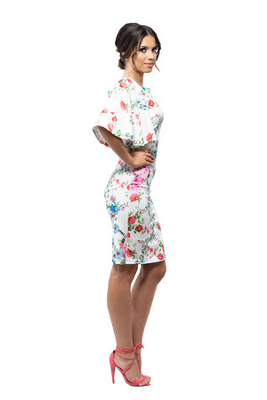 Seductive attractive tanned Latin woman in evening dress with floral pattern. Side view. Full body length portrait isolated on white background.