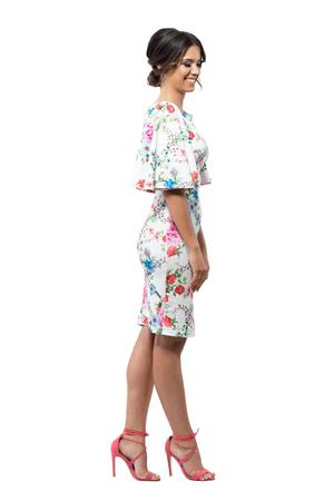 06492a87a2  80728905 - Elegante modelo femenino de moda femenina tímida en vestido  floral sonriendo y mirando hacia abajo. Vista lateral. Retrato de longitud  completa ...