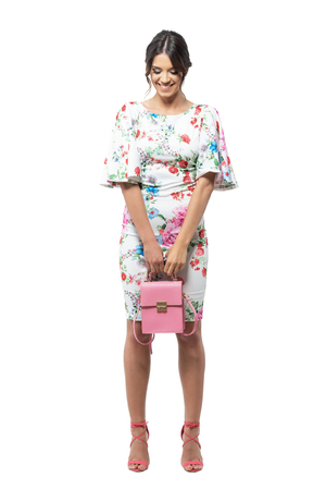 Timid shy pretty girl in floral dress with pink handbag smiling and looking down. Full body length portrait isolated on white background.