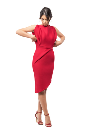 Sophisticated glamorous woman get dressed adjusting red elegant evening gown. Full body length portrait isolated on white background.