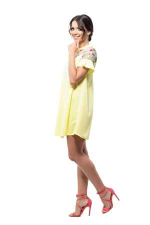 Gorgeous cute woman in yellow dress smiling at camera with hands on chin. Full body length portrait isolated on white background. Stock Photo
