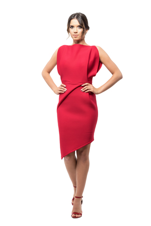 Gorgeous young woman in red dress posing with hands on hips looking at camera.  Full body length portrait isolated on white studio background.