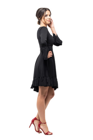 Side view of tanned Hispanic woman in black dress posing at camera touching hair.  Full body length portrait isolated on white studio background.
