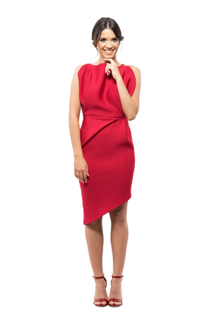 Shy timid young woman in red elegant dress smiling at camera with hand under chin.  Full body length portrait isolated on white studio background.