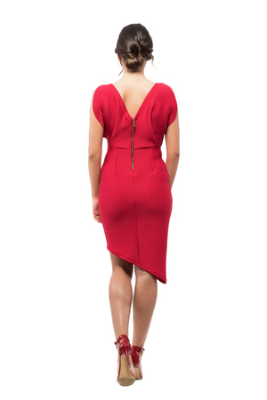 Rear view of elegant woman with bun hairstyle in red evening dress walking away. Full body length portrait isolated on white studio background.