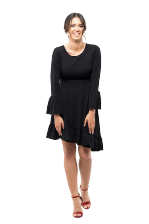 Spontaneous laughing young Latin woman in black flounce dress.  Full body length portrait isolated on white studio background.