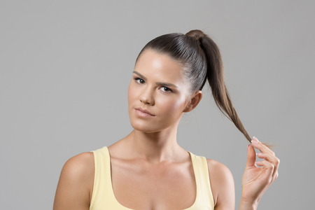 likeable: Confident sporty fit woman twirling ponytail hair lock looking at camera over gray studio background.