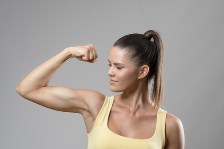 flexing: Strong sporty fit woman in yellow tank top flexing bicep muscle over gray studio background. Stock Photo