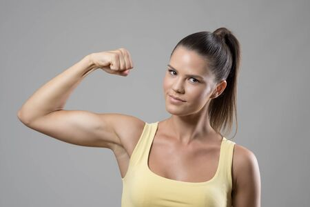 likeable: Young fit sporty woman in singlet with ponytail flexing biceps arm muscle looking at camera over gray studio background. Stock Photo