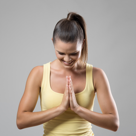 Fit sporty woman in prayer namaste hand gesture smiling and looking down over gray studio background.