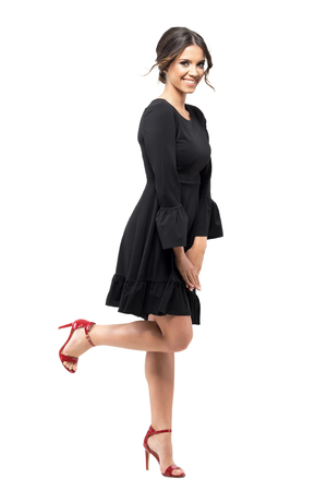 Windy dress and hair motion of young excited woman smiling with leg raised up. Full body length portrait isolated on white background. Stock Photo