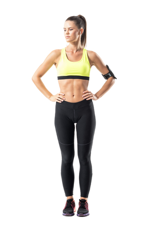 Confident proud athletic sporty female jogger with hands on waist looking down. Full body length portrait isolated on white background. Stock Photo