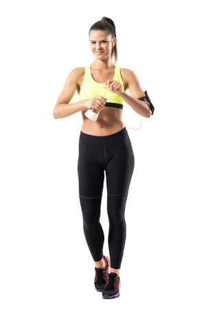Sporty fit woman in yellow tank top and legging opening water bottle and smiling at camera. Full body length portrait isolated on white background.