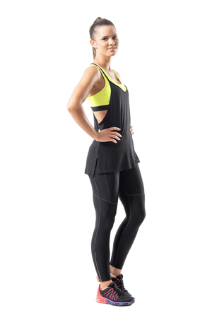 Active young sportswoman in black tank top and leggings side view. Full body length portrait isolated on white background.