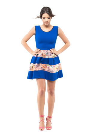 Cute woman in  blue summer dress looking down with windy flying hair.  Full body length portrait isolated on white studio background.