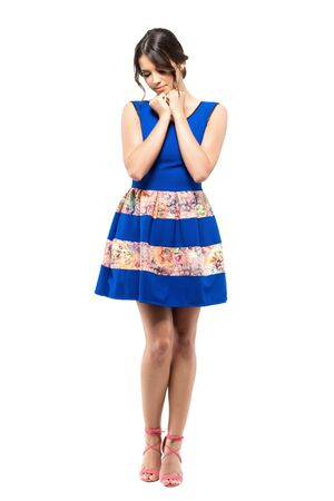 Tender sad feminine beauty in blue summer dress looking down with head on hands.  Full body length portrait isolated on white studio background. Stock Photo