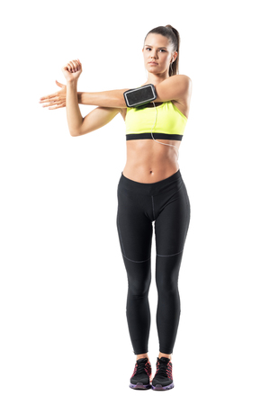 ear buds: Young female jogger warming up doing shoulder exercise while stretching arm. Full body length portrait isolated on white studio background