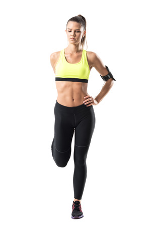 Front view of athletic young pretty woman jogger stretching leg muscles exercise. Full body length portrait isolated on white studio background Stock Photo