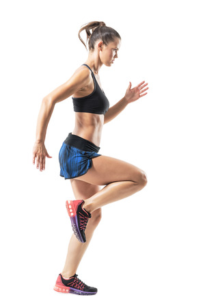 Focused athletic female sprinter movement run and looking ahead. Full body length portrait isolated on white studio background. Stock Photo