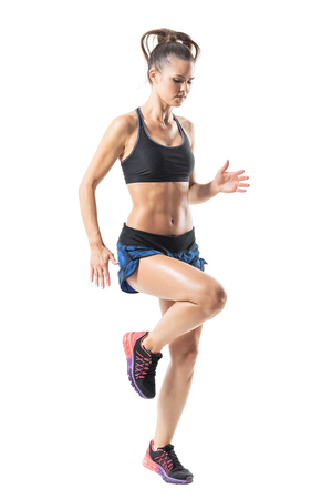Action motion of female athlete sprinting and looking down. Half profile. Full body length portrait isolated on white studio background.