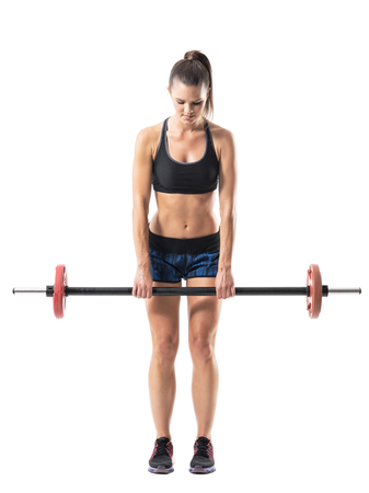 Front view of strong muscular athletic woman doing dead lift exercise with barbell. Full body length portrait isolated on white studio background.