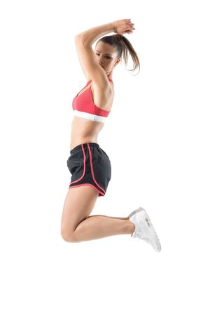 Side view of fit active sporty woman jumping in mid air looking back over shoulder. Full body length portrait isolated on white studio background.