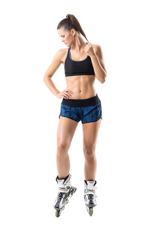 Mujer joven deportiva apta confiada en los pcteres de ruedas que tocan la cola de caballo que mira abajo. Retrato de cuerpo entero aislado sobre fondo blanco de estudio. Foto de archivo