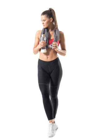 pantalones abajo: Confident healthy sportswoman in sportswear with towel and glass water bottle looking down. Full body length portrait isolated on white background.