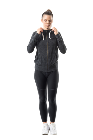 pantalones abajo: Woman runner in zip up hoodie sweatshirt get ready for running looking down. Full body length portrait isolated on white background.