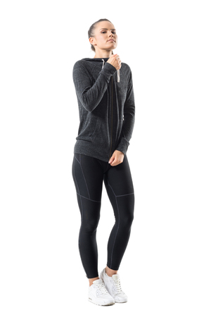 Gorgeous confident sporty woman zipping zip up hooded sweatshirt looking at camera. Full body length portrait isolated on white background. Stock Photo
