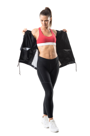 pantalones abajo: Active fit woman in leggings taking off tracksuit jacket showing abs. Full body length portrait isolated on white background.