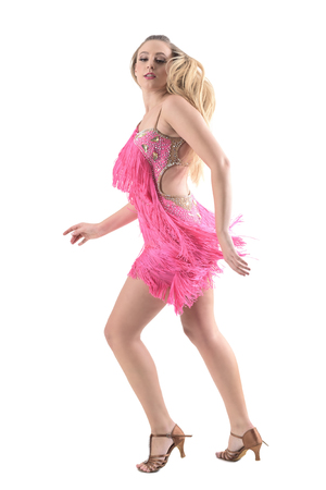 Side view of blonde woman dancing bachata turning at camera looking down. Full body length portrait isolated on white studio background.