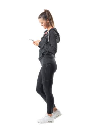 Vista lateral de la mujer joven feliz del corredor del ajuste que usa el teléfono móvil y la sonrisa. Retrato de cuerpo entero aislado sobre fondo blanco.