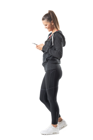 Side view of young happy fit runner woman using mobile phone and smiling. Full body length portrait isolated on white background. Stockfoto