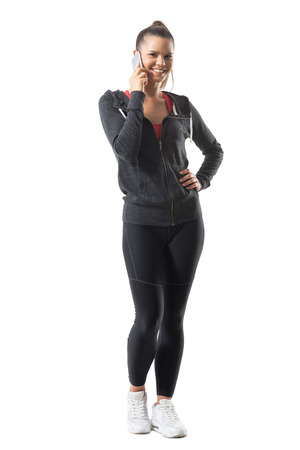 Happy smiling young fit woman in sports clothing talking on the phone looking at camera. Full body length portrait isolated on white background.