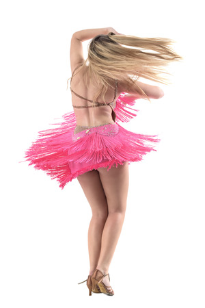 Motion of rear view latino blonde woman dancing with flowing hair and dress fringes. Full body length portrait isolated on white studio background.