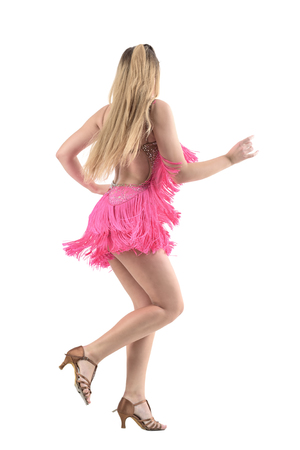 Rear view of sexy blonde latino dancer doing salsa dance steps. Full body length portrait isolated on white studio background. Stock Photo