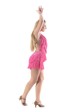 Side view of woman dancing latino dances with arms raised above head posture. Full body length portrait isolated on white studio background.
