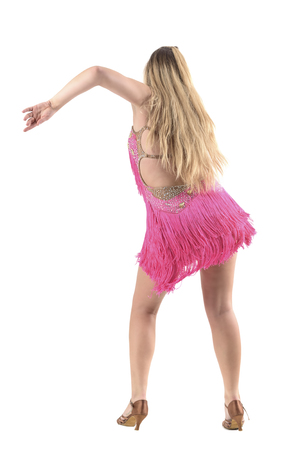 Skillful professional latino dancer in pink fringed costume dancing back view. Full body length portrait isolated on white studio background.